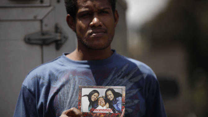 "William Montoya, 28, a supporter of Venezuela's President Hugo Chavez, holds a picture of Chavez with his daughters, Maria Gabriela, left, and Rosa Virginia that reads in Spanish ""We shall overcome!"" as he stands outside the military hospital where Chavez is allegedly receiving treatment, in Caracas, Venezuela, Wednesday, Feb. 20, 2013. Chavez's sudden return to Venezuela after more than two months of cancer treatments in Cuba has fanned speculation that the president could be preparing to relinquish power and make way for a successor and a new election. (AP Photo/Ariana Cubillos)"