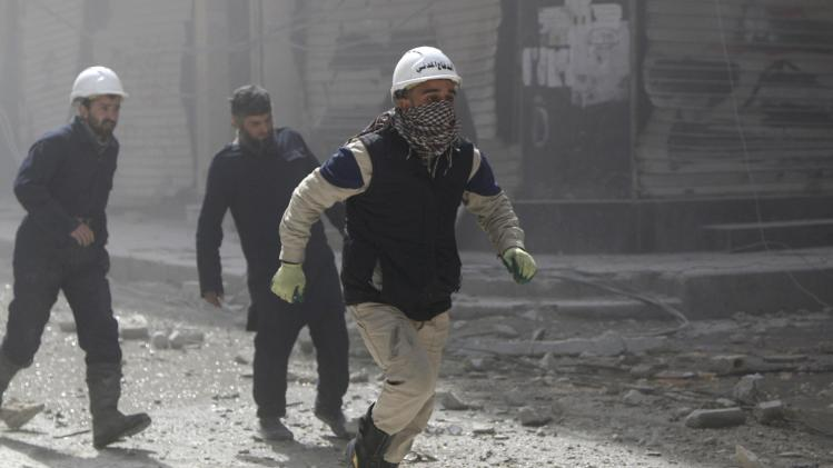 Civil defence members run towards a site hit by what activists said were barrel bombs dropped by forces loyal to Syria's President Bashar al-Assad in Aleppo