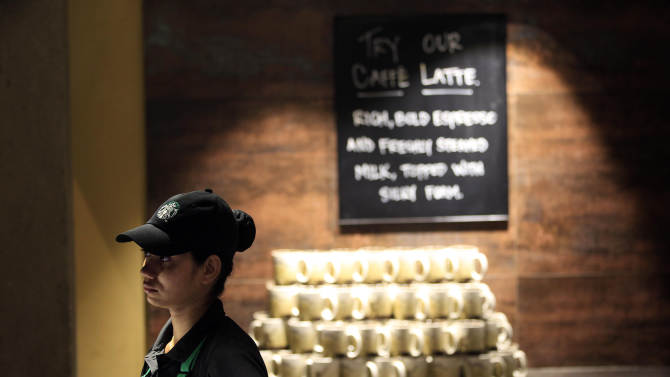 An Indian employee of the newly inaugurated first India outlet of Starbucks stands at the store in Mumbai, India, Friday, Oct. 19, 2012. Starbucks inaugurated its first store in India Friday in a historic building in southern Mumbai as the Seattle-based coffee giant seeks growth in a market long associated with tea drinkers. (AP Photo/Rajanish Kakade)