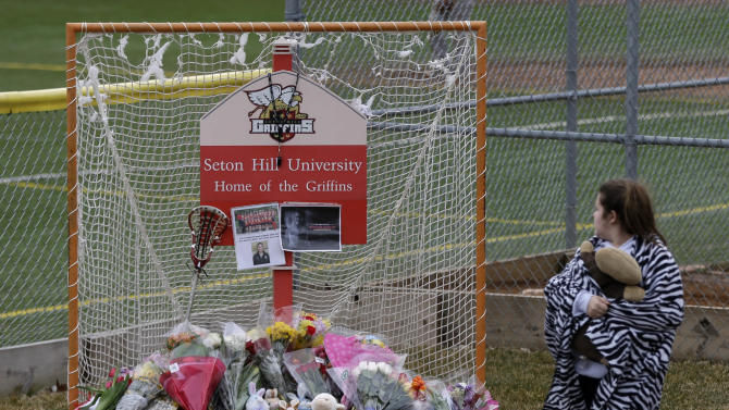 A visitor to the Seton Hill University campus walks past lacrosse goal serving as a memorial for Seton Hill University's women's lacrosse coach Kristina Quigley on the school's  Greensburg, Pa. campus, Sunday, March 17, 2013. Coach Quigley and the tour bus driver were killed when a tour bus carrying three coaches and members of the Seton Hill women's lacrosse team crashed at about 9 a.m., Saturday morning on the Pennsylvania turnpike, spokeswoman Renee Colborn said. It's not clear what caused the crash, but state police were investigating, said Megan Silverstram of the Cumberland County public safety department. (AP Photo/Gene J. Puskar)