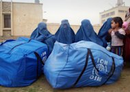In this Thursday, Nov. 24, 2011, Afghan women clad in burqas sit near their packed bags of humanitarian aid donated by International Organization for Migration (IOM) for drought-hit families in Mazar-e-Sharif, Balkh province, north of Kabul, Afghanistan. The United Nations appealed for $142 million on Oct. 1 to help those hit by the drought in 14 northern provinces where up to 80 percent of non-irrigated fields yielded little to no crops. So far, about $49 million has been pledged by aid groups, the U.S. and European nations. (AP Photo/Mustafa Najafizada)
