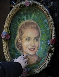 A woman touchs a portrait of Eva Duarte de Peron at the Duarte&#39;s Family vault where rest the remains of Eva Duarte de Peron on the 60th anniversary of her death in Buenos Aires