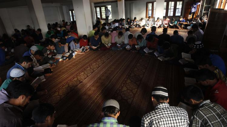 Kashmiri Muslims read the Koran during the holy month of Ramadan inside Rahat Manzil in Srinagar