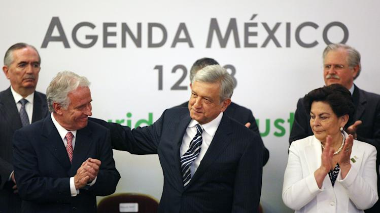 Andres Manuel Lopez Obrado, presidential candidate of the Democratic Revolution Party, PRD, center, and Mexican businessman Alejandro Marti, left front, during an event hosted by the non-governmental organization Mexico SOS, that advocates security and justice, in Mexico City, Monday April 2, 2012. The four candidates for Mexico's presidency officially launched their campaigns for the July 1 election on Friday, all of them promising change. (AP Photo/Alexandre Meneghini)