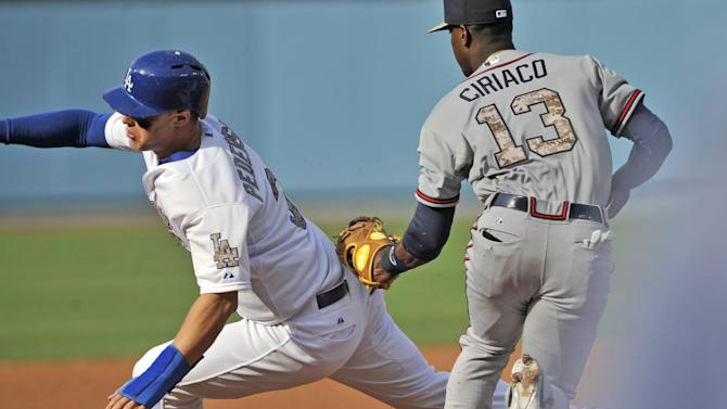 Atlanta Braves third baseman Pedro Ciriaco, right, tags out Los Angeles Dodgers Joc Pederson on a fielder's choice during the first inning of a baseball game in Los Angeles, Monday, May 25, 2015. (AP Photo/Richard Hartog)