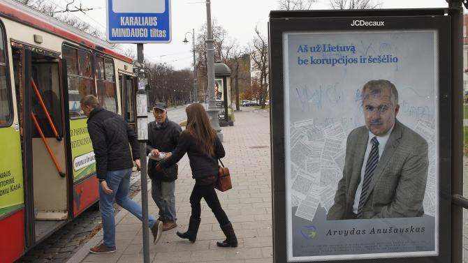 Local residents hurry to board a bus at a bus stop with an election poster of Homeland Union party member Arvydas Anusauskas in the foreground, in Vilnius, Lithuania, Thursday Oct. 27, 2012. The poster reads: ''I am for Lithuania without corruption''. Lithuanians will cast ballots in the second-round of national elections Sunday in a tight race that could ultimately determine how quickly the small Baltic nation introduces the euro and whether it will build a new nuclear power plant. (AP Photo/Mindaugas Kulbis)