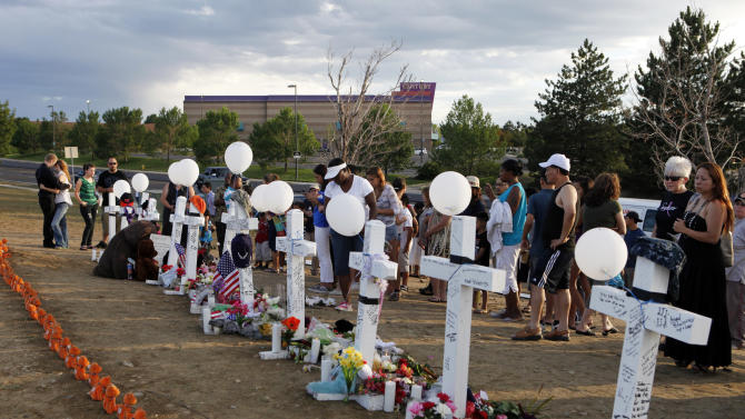 People visit a memorial for the victims in the shooting across the street from the Century 16 movie theater in Aurora, Colo., Sunday, July 22, 2012. James Eagen Holmes has been charged in the shooting at the Aurora theater early Friday that killed twelve people and injured more than 50.He is scheduled to appear in court Monday morning. (AP Photo/Ed Andrieski)