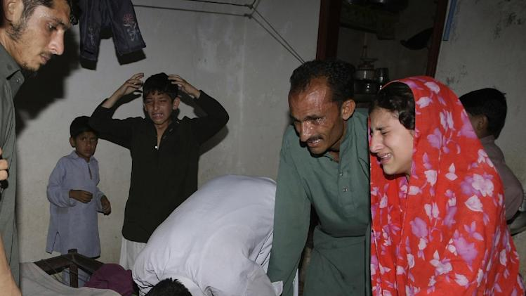 People mourn the death of their family member in a blast in Karachi, Pakistan Friday, April 26, 2013.  A bomb planted near the office of a political party threatened by the Taliban has killed many people in southern Pakistan, police said. (AP Photo/Fareed Khan)