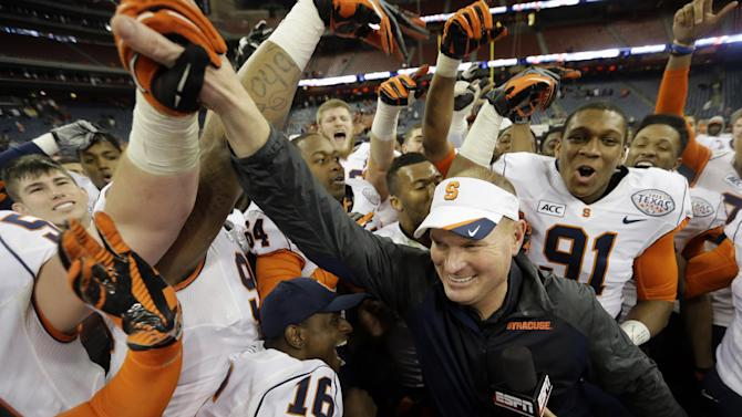 Syracuse coach Scott Shafer, right, celebrates with his team after winning the Texas Bowl NCAA college football game against Minnesota, Friday, Dec. 27, 2013, in Houston. Syracuse won 21-17