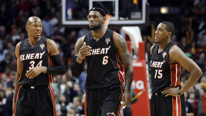 Miami Heat forward LeBron James, center, and guard Mario Chalmers, right, listen to guard Ray Allen during the second half of an NBA basketball game against the Chicago Bulls in Chicago on Wednesday, March 27, 2013. The Bulls won 101-97, ending the Heat's 27-game winning streak. (AP Photo/Nam Y. Huh)