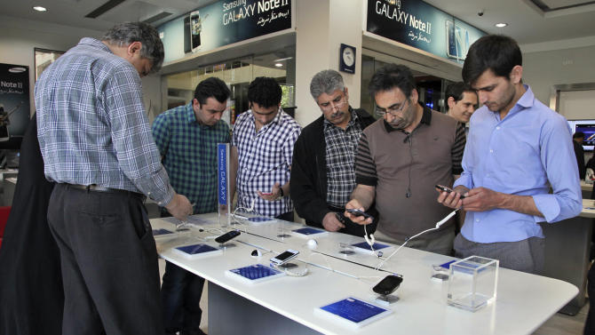 "Potential customers try out Samsung cell phones in a store in Tehran, Iran, Thursday, April 25, 2013. Iranian users of Samsung mobile applications are saying they have been notified that their access to the company's online store will be denied from May 22. In the message, Samsung said it cannot provide access to the store in Iran because of ""legal barriers."" (AP Photo/Vahid Salemi)"