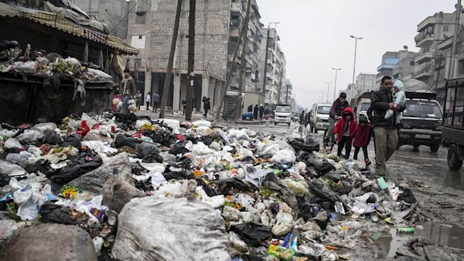 A family crosses a street piled with rubbish in Aleppo, Syria, Saturday, Jan. 5, 2013. The revolt against President Bashar Assad started in March 2011 began with peaceful protests but morphed into a civil war that has killed more than 60,000 people, according to a recent United Nations recent estimate. (AP Photo/Andoni Lubaki)