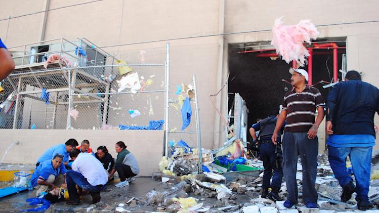 Rescue workers help an injured person, left, after an explosion at a candy factory in Ciudad Juarez, Mexico, Thursday, Oct. 24, 2013. The explosion happened at the Dulces Blueberry factory and caused a floor to collapse, said factory worker Ismael Bouchet. (AP Photo/Raymundo Ruiz)