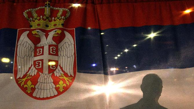 A man stands behind the Serbian national flag Mitrovica on the evening of April 19, 2013