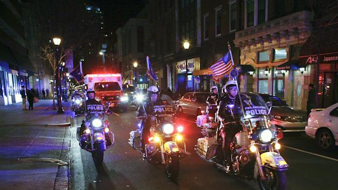 Police escort an ambulance carrying the body of fallen firefighter Capt. Michael Goodwin from Thomas Jefferson Hospital in Philadelphia, early Sunday, April 7, 2013. The fire caused a partial roof collapse that killed Goodwin and injured a colleague who was trying to rescue him, officials said. (AP Photo/ Joseph Kaczmarek)