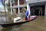 Don Duplantier paddles a pirogue from his flooded home as floodwaters from Hurricane Isaac recede in Braithwaite, La., Sunday, Sept. 2, 2012. Duplantier had retrieved his cat and had collected his daughter&#39;s bridesmaid dress for the upcoming wedding of his son. (AP Photo/Gerald Herbert)