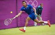 France's Jo-Wilfried Tsonga plays a return to Canada's Milos Raonic during their men's single tennis second round match during the 2012 London Olympic Games at the All England Tennis Club in Wimbledon, southwest London. Tsonga won 6-3, 3-6, 25-23