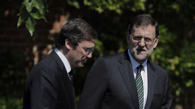 Spain's Prime Minister Mariano Rajoy, right and Portugal's Prime Minister Pedro Passos Coelho, left, arrive to review troops during a welcome ceremony, prior to a meeting at the Moncloa Palace, in Madrid, Monday, May 13, 2013. (AP Photo/Andres Kudacki)