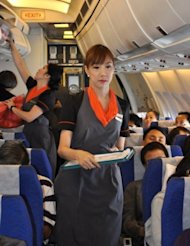Transsexual fight attendant Chayathisa Nakmai (right) works onboard a Thai PC Air flight between Bangkok and Hong Kong on March 9. Fledgling Thailand-based carrier PC Air has hired four transgender cabin crew in a highly publicised recruitment drive that has divided opinion over whether the move is in the spirit of equality or exploitation