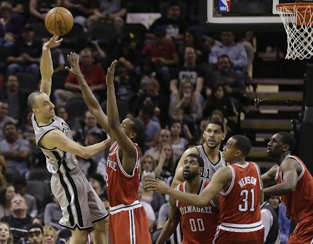 San Antonio Spurs' Manu Ginobili, left, of Argentina, passes the ball over Milwaukee Bucks' Khris Middleton (22) during the second half of an NBA basketball game, Sunday, Jan. 19, 2014, in San