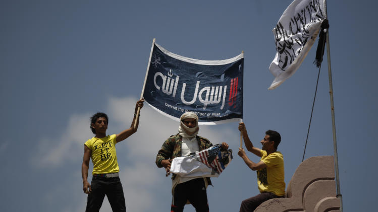 "A Yemeni protestor, center, destroys an American flag pulled down as other hold a banner in Arabic that reads, ""any one but you God's prophet"" at the U.S. Embassy compound during a protest about a film ridiculing Islam's Prophet Muhammad, in Sanaa, Yemen, Thursday, Sept. 13, 2012. Dozens of protesters gather in front of the US Embassy in Sanaa to protest against the American film ""The Innocence of Muslims"" deemed blasphemous and Islamophobic. (AP Photo/Hani Mohammed)"