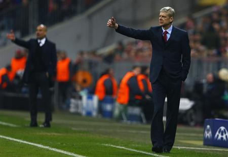 Arsenal's coach Wenger reacts next to Bayern Munich's coach Guardiola during their Champions League round of 16 second leg soccer match in Munich