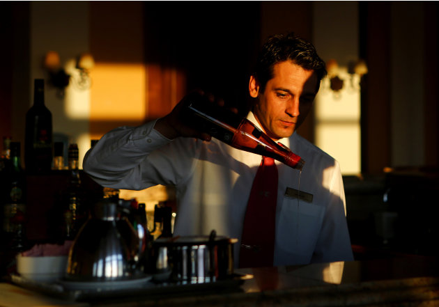 Vassilis Vassilakis prepares drinks at the bar of the Olympia Oasis Hotel at the Olympia Riviera resort in the town of K... Yannis Behrakis / Reuters