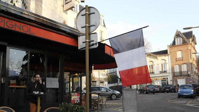 A French flag hangs from a cafe in Ville d'Avray, outside Paris, Friday, Nov. 27, 2015. French President Francois Hollande called on his compatriots to hang French tricolor flags on Friday to pay homage to the 130 victims of the Nov. 13 attacks, an unusual appeal by a Socialist leader in a country where flag-waving is often associated with nationalists and the far right. (AP Photo/Bertrand Combaldieu)