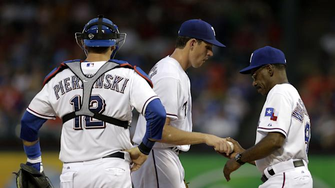 Texas Rangers catcher A.J. Pierzynski (12) watches as starting pitcher Nick Tepesch hands the ball over to manager Ron Washington in the fourth inning of a baseball game against the Oakland Athletics, Monday, June 17, 2013, in Arlington, Texas. (AP Photo/Tony Gutierrez)