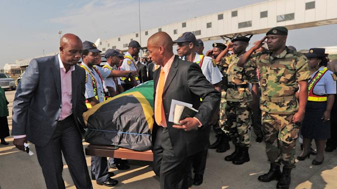 The remains of journalist Nat Nakasa, in a coffin draped in a South African flag, arrives in Durban, South Africa, Tuesday, Aug. 19, 2014 where he will be reburied, South Africa's arts and culture ministry said. South Africa is repatriating the remains of Nakasa, a black anti-apartheid journalist, who died in the United States in 1965 and was buried there until his recent exhumation. (AP Photo)