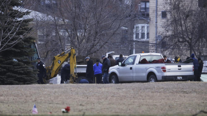 A backhoe is seen at Rosehill Cemetery in Chicago, Friday, Jan. 18, 2013, as workers begin the process of exhuming the body of Urooj Khan who was poisoned with cyanide after winning the lottery. Khan died in July as he was about to collect $425,000 in lottery winnings. His death was initially ruled a result of natural causes, but a relative pressed for a deeper look and his death was reclassified as a homicide.  (AP Photo/M. Spencer Green)
