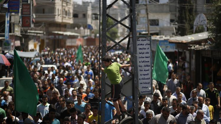 Palestinian boy climbs an electrical pole as mourners march during the funeral of the wife of Deif, his infant son Ali and other Palestinians in the Gaza Strip