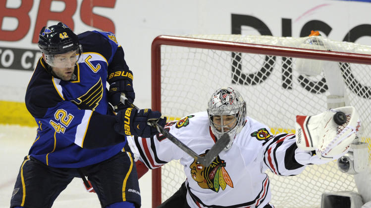 Chicago Blackhawks' goalie Corey Crawford, right, makes a glove-save against St. Louis Blues' David Backes (42) during the second period in Game 2 of a first-round NHL hockey playoff series on Saturday, April 19, 2014, in St. Louis