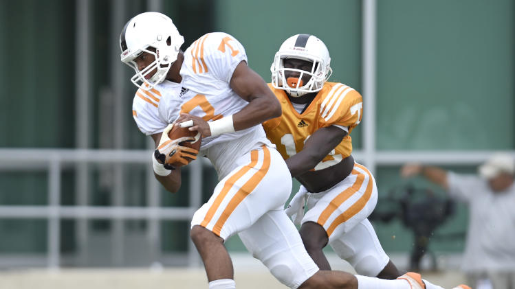 In this photo taken on Friday, Aug. 8, 2014, Tennessee wide receiver Josh Malone, left, is trailed defensive back Emmanuel Moseley during NCAA college football practice  in Knoxville, Tenn