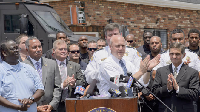 New Orleans Mayor Mitch Landrieu claps at a press conference at North Villere and Frenchman Streets where the mayor talked about the capture of Akein Scott, who shot 20 people in a the Original Big 7 Social Aid and Pleasure Club Inc. parade on Mother's Day, in New Orleans, Thursday, May 16, 2013. Landrieu and police chief Ronal Serpas, behind Landrieu, hailed the police work as proof of officials' determination to end sporadic violence that mars the image of the tourism-dependent city. (AP Photo/Matthew Hinton)