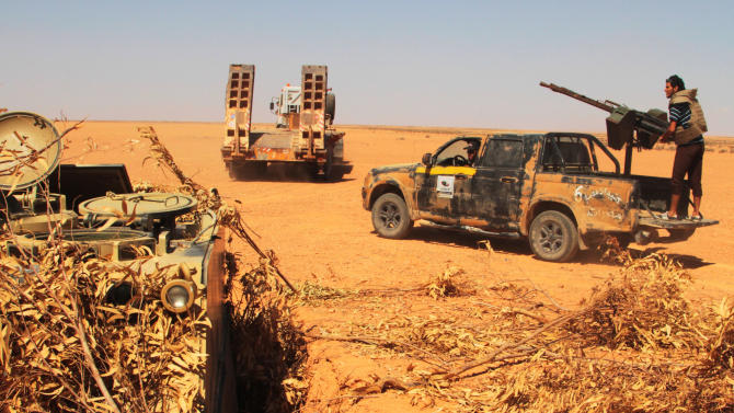 Rebel  fighters take control of  a military vehicle, left,  positioned to defend what used to be Gadhafi's 32nd infantry regiment's base at Mardun, some 10 kilometers from the outskirts of Ban Walid, Libya, Wednesday, Sept. 7, 2011. (AP Photo/Gaia Anderson)