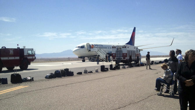 """In this photo provided by passenger Tim Cole, a Delta Air Lines jet en route to San Diego from Detroit sits at a remote area of Albuquerque International Sunport, Sunday, May 8, 2011, in Albuquerque, N.M., as some of the passengers standby at right, and their carry-on luggage is seen laid out on the tarmac for inspection after the flight was diverted due to a """"potential security threat."""" (AP Photo/Tim Cole)"""