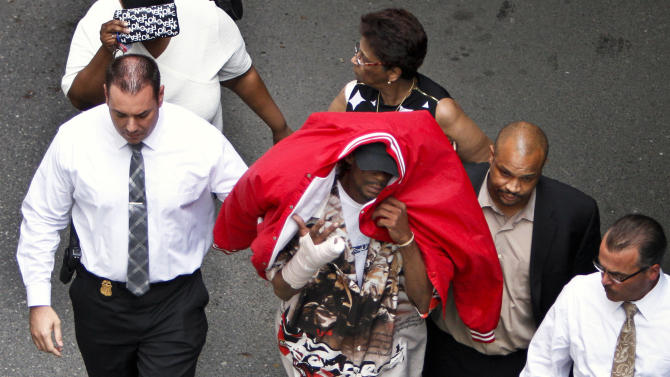 Sean Benschop, center, with red jacket over his head, walks with investigators as he arrives at the Philadelphia Police Department's Central Detectives Division, Saturday June 8, 2013, in Center City Philadelphia. Benschop, the heavy equipment operator with a lengthy rap sheet accused of being high on marijuana when a downtown building collapsed onto a thrift store, killing six people, turned himself in on Saturday to face charges in the deaths, police said. (AP Photo/ Joseph Kaczmarek)