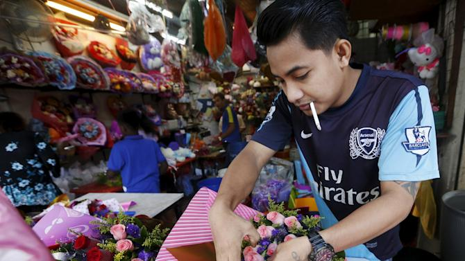 A man prepares roses for sale ahead of Valentine's Day in Kuala Lumpur