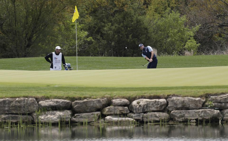 Matt Kuchar, right, chips onto the third green during the second round of the Texas Open golf tournament on Friday, April 5, 2013, in San Antonio.  (AP Photo/Eric Gay)