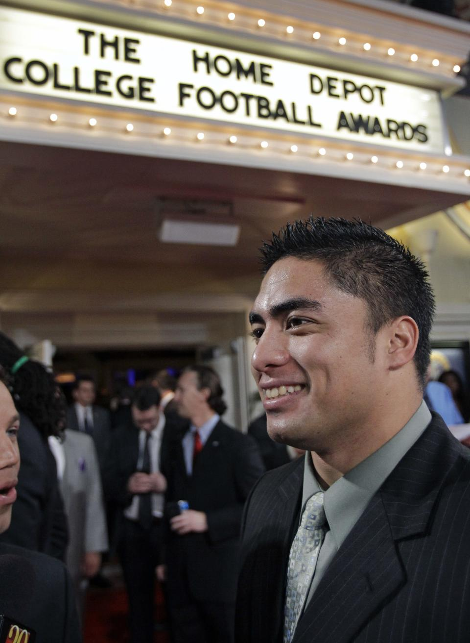 Notre Dame's Manti Te'o talks with reporters as he arrives at the Home Depot College Football Awards in Lake Buena Vista, Fla., Thursday, Dec. 6, 2012.(AP Photo/John Raoux)