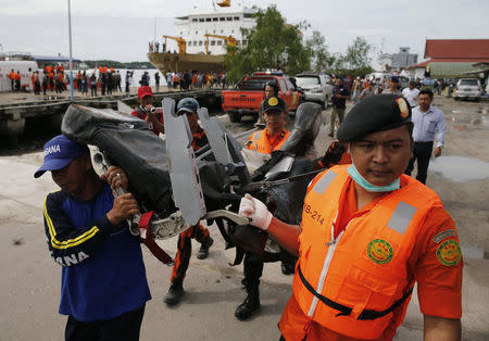 Rescue team members walk as they carry the wreckage of a seat of the AirAsia Flight QZ8501 airliner at Kumai port