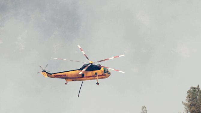 A firefighting helicopter flies into a smoke covered canyon to drop its load of retardant on the Ponderosa Fire near Paynes Creek, Calif., Wednesday, Aug. 22, 2012. The Ponderosa Fire, which has scorched about 38 square miles since Saturday, was 50 percent contained Wednesday morning, according to the California Department of Forestry and Fire Protection. The threat to homes about 35 miles east of Redding has dropped from 3,500 earlier this week to roughly 200 residences. (AP Photo/Rich Pedroncelli)
