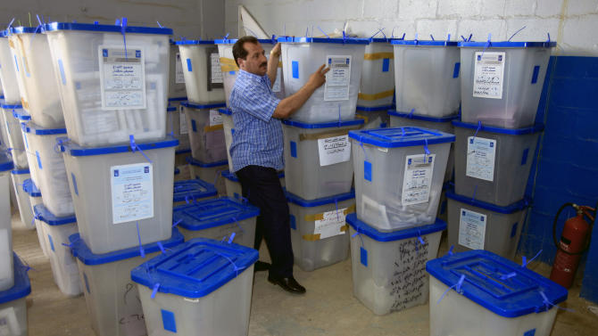 An electoral worker carries ballot boxes at a counting center in Baghdad, Iraq, Sunday, April 21, 2013. Iraqis have begun counting votes from the first provincial elections since the last U.S. troops withdrew in December 2011. (AP Photo/ Karim Kadim)