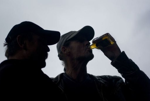 <p>A man watches his friend as he drinks from a bottle of rum on a street in Prague. At least 14 people have died and more than 20 have been hospitalised in the Czech Republic after drinking spirits apparently tainted with methanol, Czech officials said.</p>