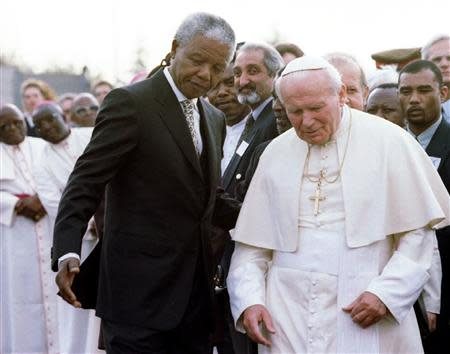 File picture shows South African President Nelson Mandela guiding Pope John Paul II after they met at Johannesburg International Airport