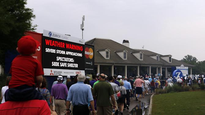 Fans exit the course as play is suspended due to severe weather during the third round of the Zurich Classic PGA golf tournament, Saturday, April 25, 2015, in Avondale, La. (AP Photo/Butch Dill)