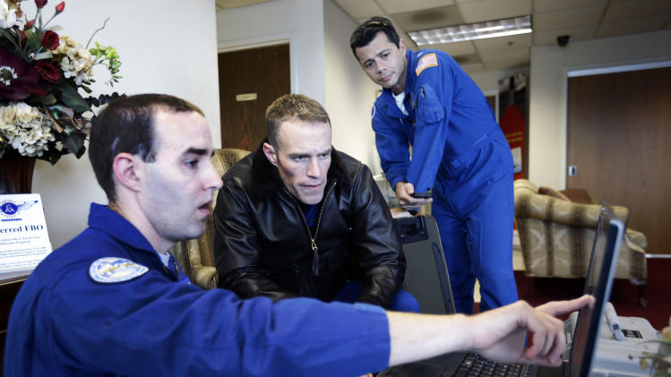 Lead Sensor Operator Andrew Halbach, left, pilot Lt. Com. Scott Price, center, and pilot Com. Al Girimonte plan a National Oceanic and Atmospheric Administration flight to document coastal changes after Superstorm Sandy, Thursday, Nov. 1, 2012 in New Castle, Del. (AP Photo/Alex Brandon)