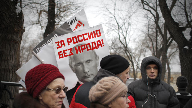 "People carry a posters of Russian President Vladimir Putin with the words reading ""For Russia without Herod!"" during a protest rally in Moscow, Russia, Sunday, Jan. 13, 2013. Some thousands of people are gathering in central Moscow for a protest against Russia's new law banning Americans from adopting Russian children, some carrying posters of President Vladimir Putin and members of Russia's parliament who overwhelmingly voted for the law last month, with the word ""Shame"" written in red over the faces and the demonstrators proclaim that Sunday's demonstration is a ""March Against the Scum"" who enacted the law. The reference to Herod in this poster refers to the Biblical ruler who murdered members of his own family and is guilty of initiating the killing of infants in Bethlehem during the time of Jesus. (AP Photo/Alexander Zemlianichenko)"