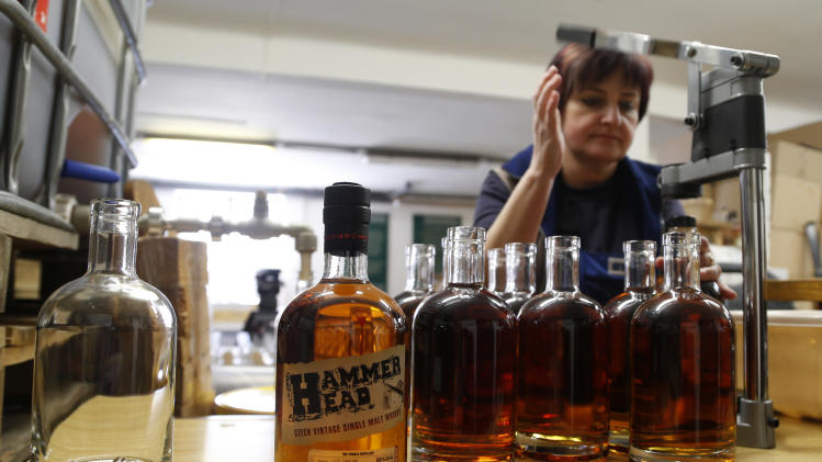 "In this Monday, April 8, 2013 photo Eva Brozovska fills bottles with single malt ""Hammer Head"" whisky in a distillery in Pradlo, Czech Republic. The ""Hammer Head"" whisky made in communist Czechoslovakia matured in oak barrels for more than twenty years to reach surprisingly good quality before hitting the market. (AP Photo/Petr David Josek)"
